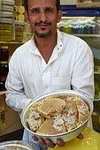 Yemeni merchant showing his honey, Taif souq, Saudi Arabia