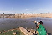 Village women looking at the birds, Demoiselle Crane (Anthropoides virgo) who winter here. Kichan, a village in the Marwari Jain community, whose inhabitants feed every winter since 1970, the wintering Cranes, Thar Desert, Rajasthan, India