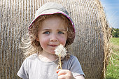 Girl blowing on a seed dandelion