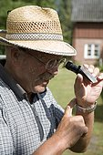 Beekeeper or apiculturist checking the honey's water and sugar content with a refractometer