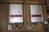 Two wall mounted Fronius IG inverters converting DC electricity from PV to AC UK
