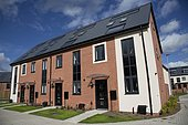 New red brick terraced houses all with solar black PV panels Persimmon Greenacres Bishops Cleeve Cheltenham UK