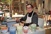 Craftswoman decorating ornamental tiles, Martine Gilles and Jaap Wieman, Brantes village, Provence, France