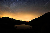 First light of dawn on the lake of the fairies, the stars are still visible, as well as a shooting star, Massif du Beaufortain, Savoie, Alps, France