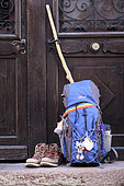 Backpack in front of the door of a cottage on which is hung a scallop shell emblem of pilgrims going to Santiago de Compostela, Saint Jean Pied de Port (64), Pyrenees, France