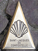 Bronze spire depicting a Saint Jacques shell inlaid in the cobblestones, indicating the direction of the pilgrimage route of Compostela, Saint Jean Pied de Port (64), Pyrenees, France