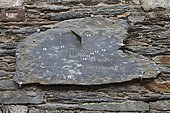 Slate solar clock on the facade of a house in La Gacilly, Brittany, France