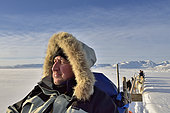 Tourist hitching sled dogs on the ice floe of Scoresbysund, Greenland