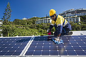 Worker cleaning solar panels, New Caledonia.