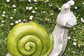 Snail on a decorative snail in a garden, spring, Pas de Calais, France