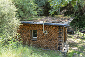 Cabin with green roof and wooden log siding, summer, Ardèche, France