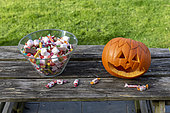 Little girls making a pumpkin for Halloween, jar of candy and pumpkin
