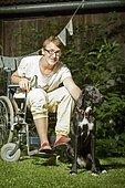 Médiation animale. Adolescent en fauteuil caressant un chien thérapeutique