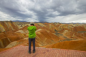 Tourist photograph, Eroded hills of sedimentary conglomerate and sandstone, Unesco World Heritage, Zhangye, China