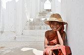 Adolescent déguisé en moine qui joue sur les marches d'une pagode en Birmanie dans la ville de Mandalay