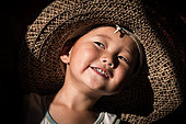 Young Kyrgyz child, with my hat lit by the sunlight in front of the door of a yurt.