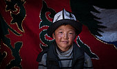 Young Kyrgyz with a kalpak, traditional hat. Image taken in a yurt in the mountains of Kyrgyzstan