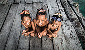 Three boys with a sea star on their head. These children are part of the Banaux or nomadic seas. They live on the Togians archipelago in Indonesia