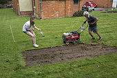 Man and teenage girl turf cutting Three Bees Community Garden April 2018 Mickleton Cotswolds UK