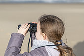 Girl observing with binoculars in winter, France
