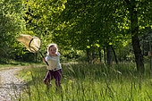 Girl having fun pursuing and catching some butterflies to observe them in a meadow, Alpes de Haute Provence, France