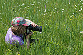 Young girl photographing orchids in a meadow, Villey St Etienne, Lorraine, France
