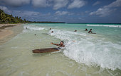 Expédition Tara Pacific - novembre 2017 Île de Yanaba, atoll d'Egum, Papouasie-Nouvelle-Guinée, enfants jouant dans les vagues avec des planches de surf fabriquées par leurs soins.