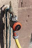 Timer installed on a garden hose, summer, Alsace, France