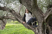 Alessandra, 7, poses in a several hundred years old olive tree in Kritsa, Crete, Greece