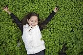 Alessandra, 7, is lying in the Bermuda buttercup in an olive grove in Kritsa, Crete, Greece