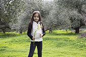 Alessandra, 7, picks Bermuda buttercup in an olive grove in Kritsa, Crete, Greece