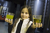 Alessandra, 7 years old, shows on one hand the filtered olive oil and in the other the unfiltered oil in the olive oil factory of Kritsa, Crete, Greece