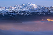 Mont Blanc and mist at dusk. Massif of Mont Blanc at dusk. First the mist is illuminated by the twilight and the light of the cities. Alps, France