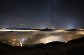 Sea of clouds lit by the Arve valley, at night, and milky way, facing the Mole mountain, the Aravis massif, and the Brasses massif. Typical autumnal stratus situation in the valleys, November 03, 2018. The clouds are illuminated by the light of the cities of the Arve. Above, the sky is clear and the Milky Way clearly visible. Scene on 180 ° (fisheye). Alps, France