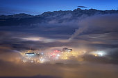 Dense fog on Grenoble and Tronche, facing the Massif de Belledonne, at dusk. Foggy situation in the early morning on Grenoble and its suburbs. The chain of the Massif de Belledonne is illuminated by the emerging daylight.
