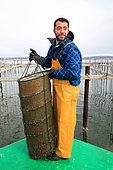 Oyster farmer handling a 'lantern', Etang de Thau, France
