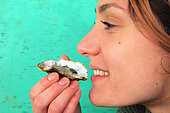 Young woman tasting an oyster Bouzigues, Etang de Thau, France
