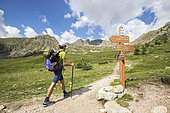 Young hiker at the intersection of the Prals Lakes Trail, Orientation Pillar, Fenestre de la Madone Valley, Haute-Vésubie, Mercantour National Park, Alpes-Maritimes, France