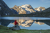 A hiker sitting on a rock contemplates the landscape at the edge of Lake Goléon (2438m) in the massif of Oisans with in the background the Meije (3983m) and the Rake (3809m), Ecrins National Park, Hautes-Alpes, France