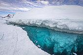 Sommet de l'iceberg émergeant de la surface de la mer gelée, il monte et descend au gré des marées et laisse l'eau libre autour de lui. Tasiilaq, Est du Groenland