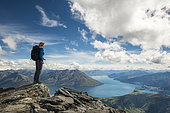 Woman on top of a mountain, view on Lake Wakatipu with city of Queenstown, Remarkables mountain range, South Island, New Zealand