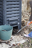 Harvesting of ripe compost in a garden composter. In commercial plastic composters, compost is harvested through the hatch at the base of the enclosure. Compost is good at harvesting when the composting elements are no longer recognizable and the compost has a black color and friable texture.