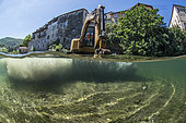Mid-air half-water view of a digger during work to restore ecological continuity on the Lergue River, Lodève, Hérault, Occitanie region, France