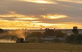 Combine harvester harvesting barley
