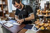 Le gérant postal de DDU Xavier tamponne des plis de philatélistes. Chaque pli demande au minimum 11 manipulations de la part du gérant postal, entre la réception par le bateau et la dépose dans la boite d'envoi. Base antarctique Dumont-d'Urville, Terre Adélie, Antarctique