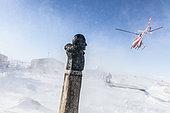 Déchargement de l'Astrolabe par hélicoptère sur la base Dumont D'urville. Buste de Paul Emile Victor, Terre Adélie, Antarctique