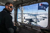 "From the lookout or ""nest of magpie"", the second captain of the Astrolabe Julien Duroussy observes high the pack to find the best route to follow to cross and not get stuck. For this he is in constant contact with the captain on the bridge via VHF. Adélie Land, Antarctica"