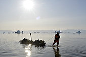 Kayaker pulling his kayak on the shoals of Scoresbysund, North East Greenland