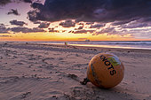Buoy stranded on the beach of Sangatte, at sunset, Hauts de France, France