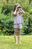 Girl watching birds in a garden with binoculars, summer, Lot, Occitanie, France